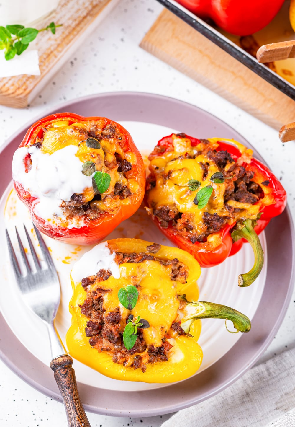 2 Red stuffed bell peppers and 1 yellow stuffed bell pepper on a plate.