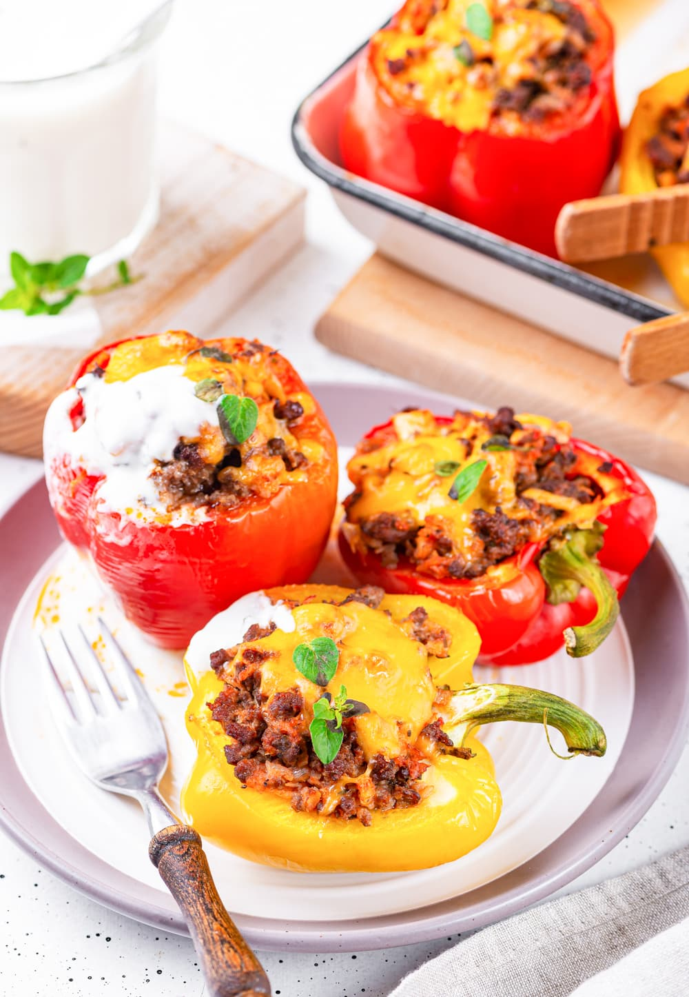 A plate filled with multiple stuffed bell peppers & one of them is topped with sour cream.