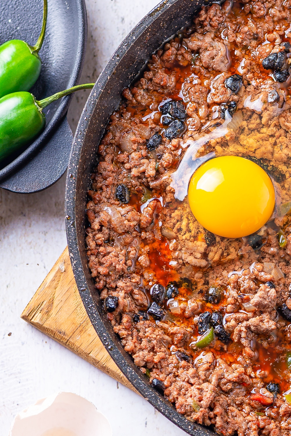 An egg in a skillet filled with ground beef and black soybeans.