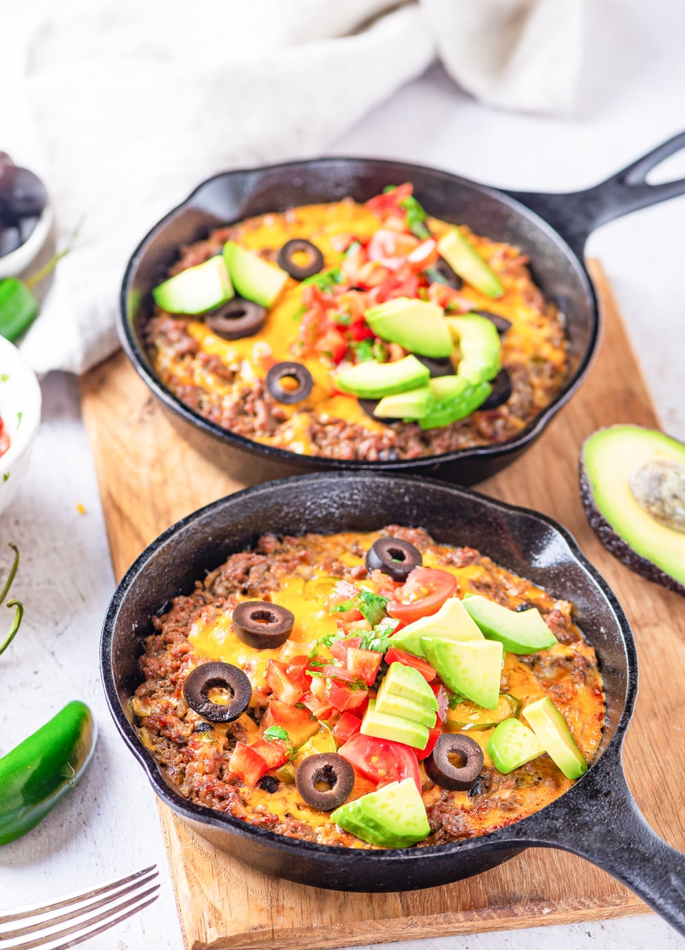 2 Cast iron pans filled with taco casserole and topped with black olives, salsa, and pieces of avocad.