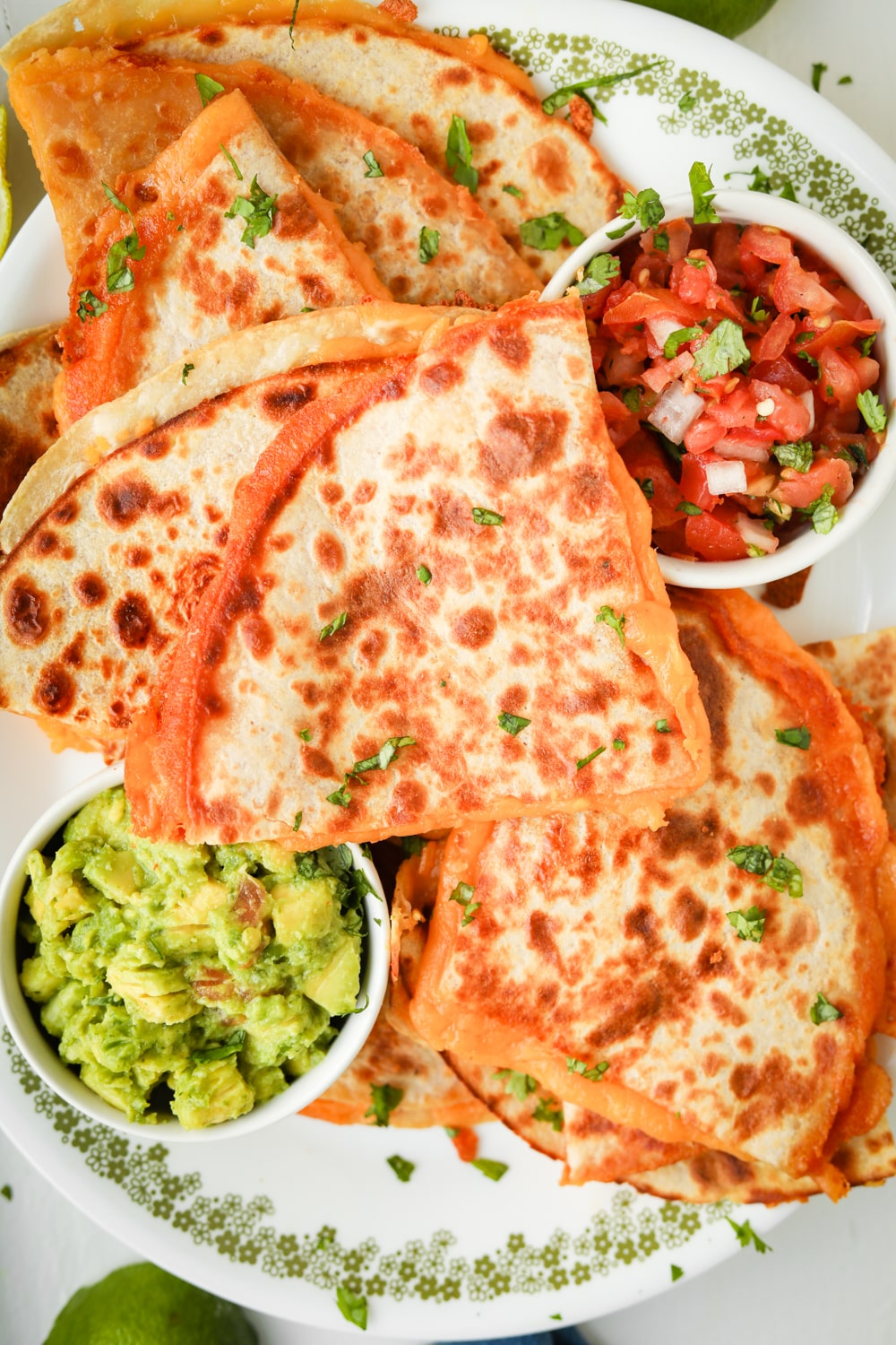 Cheddar cheese quesadillas cut up and stacked on top of each other on a white plate.