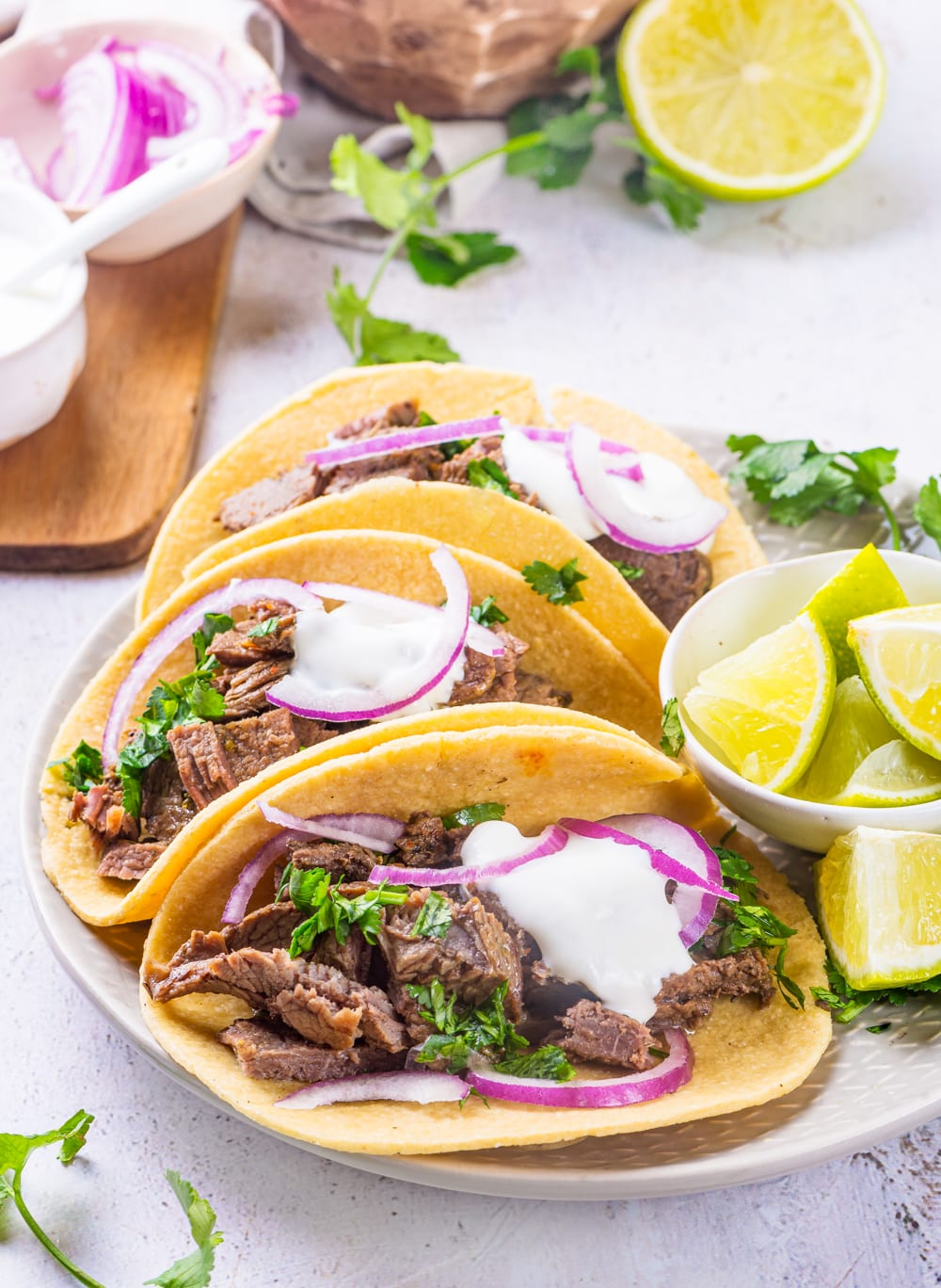 Tortillas filled with carne asada and topped with red onions and sour cream.