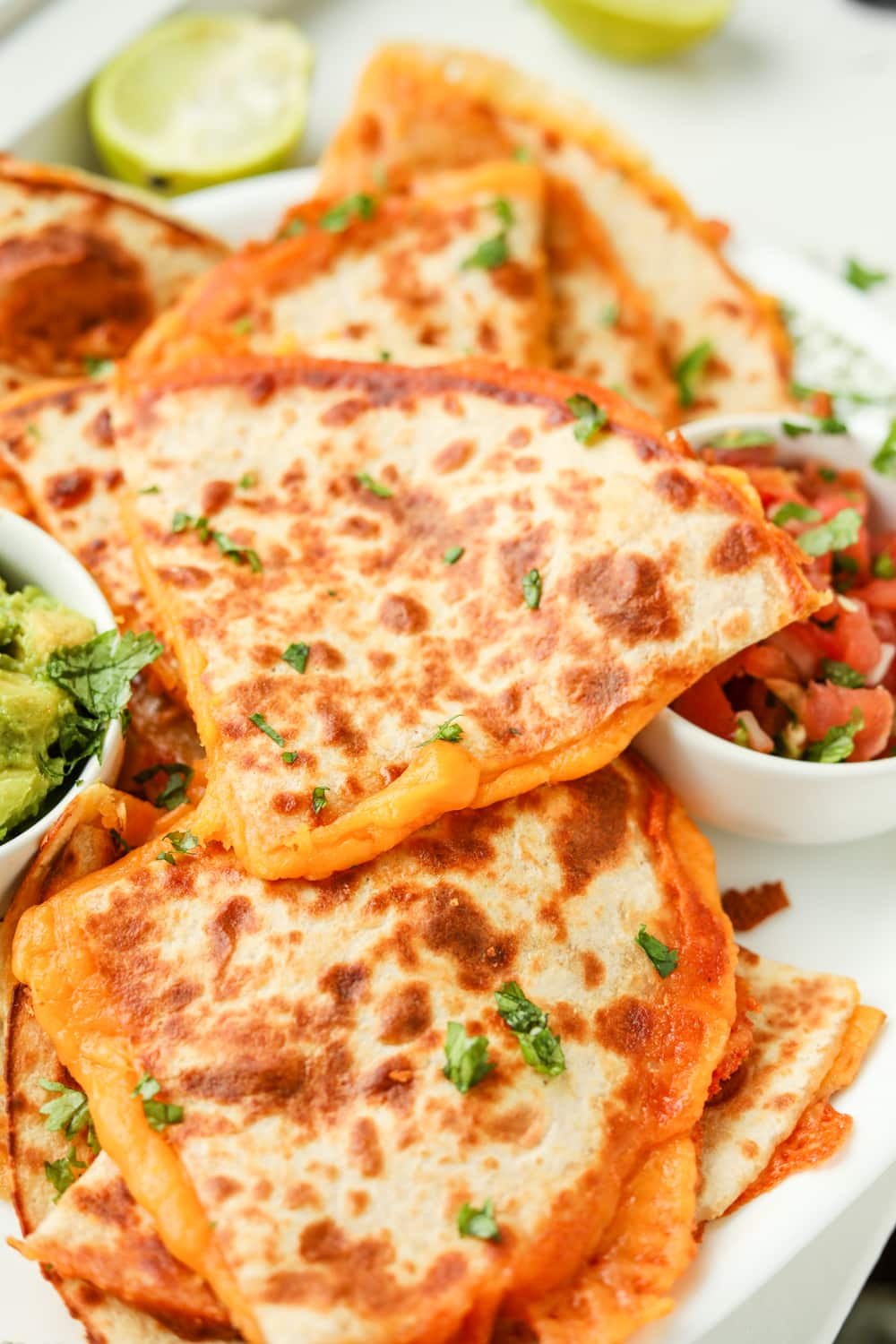 Quesadillas stuffed with cheese on a white plate.