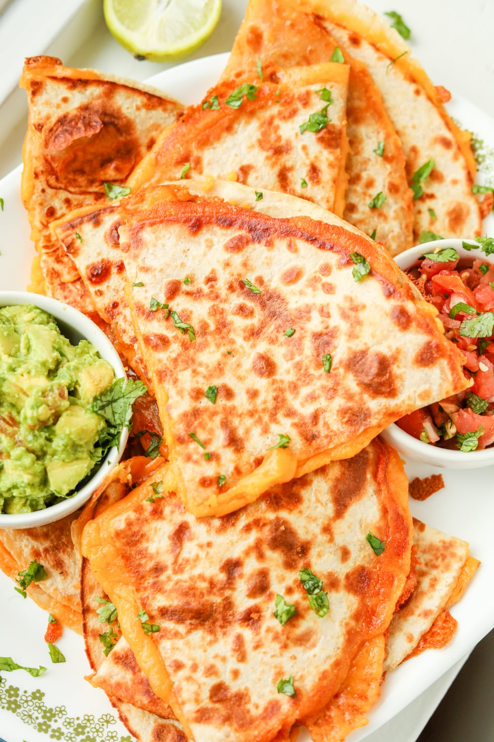Quesadillas next to sides of tomato and guacamole.