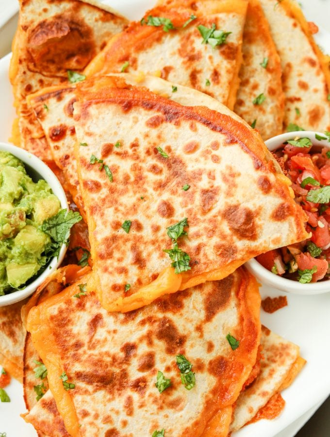 Quesadillas on a platter stacked on top of each other.