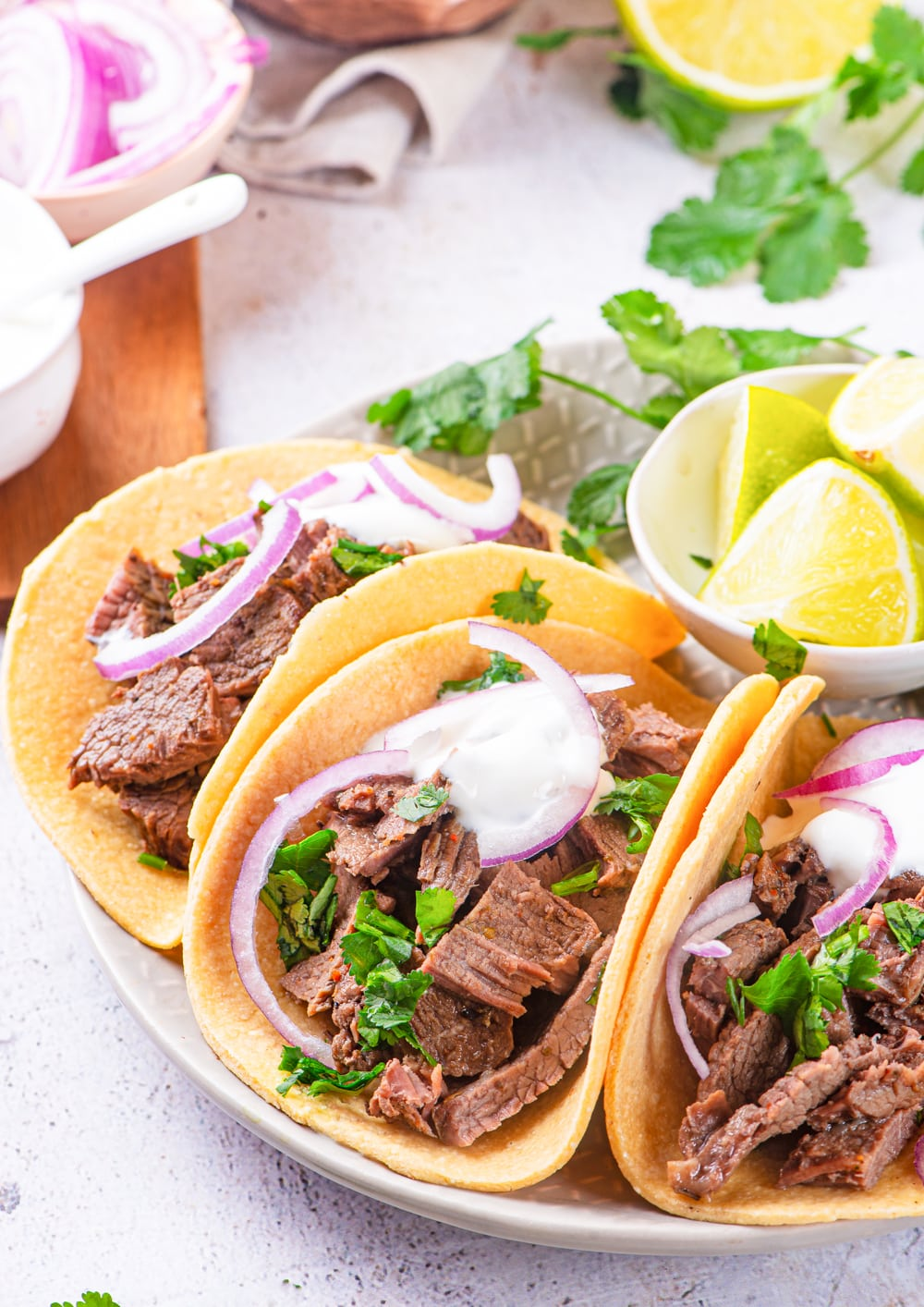 Carne Asada tacos topped with chimichurri sauce, red onions, and sour cream.