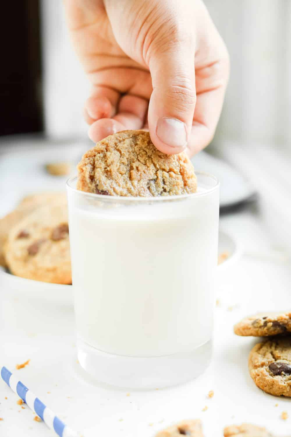 A hand dipping half of a chocolate chip cookie in a glass of milk.