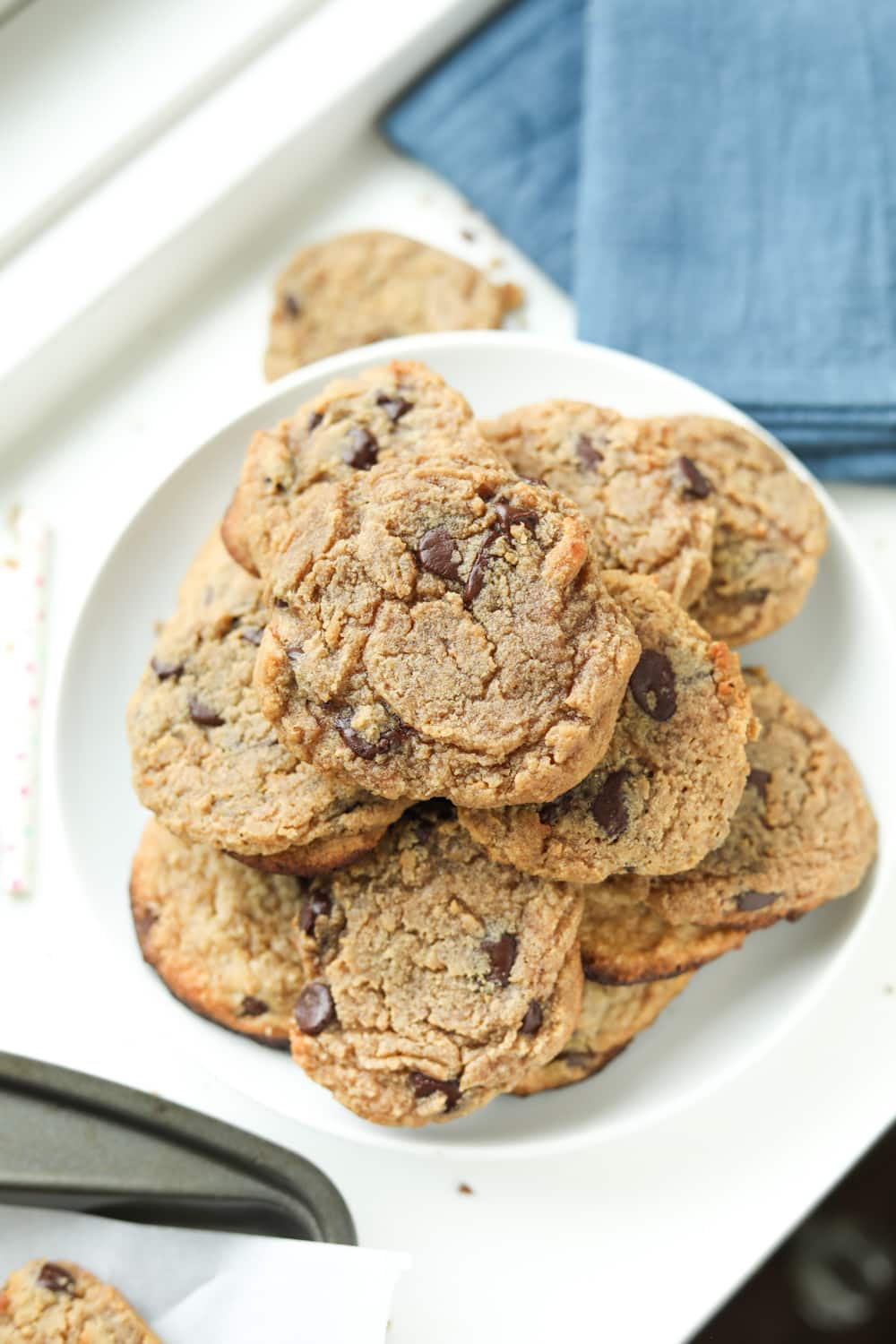 Chocolate chip cookies staked on top of each other on a white plate, next to a blue napkin.