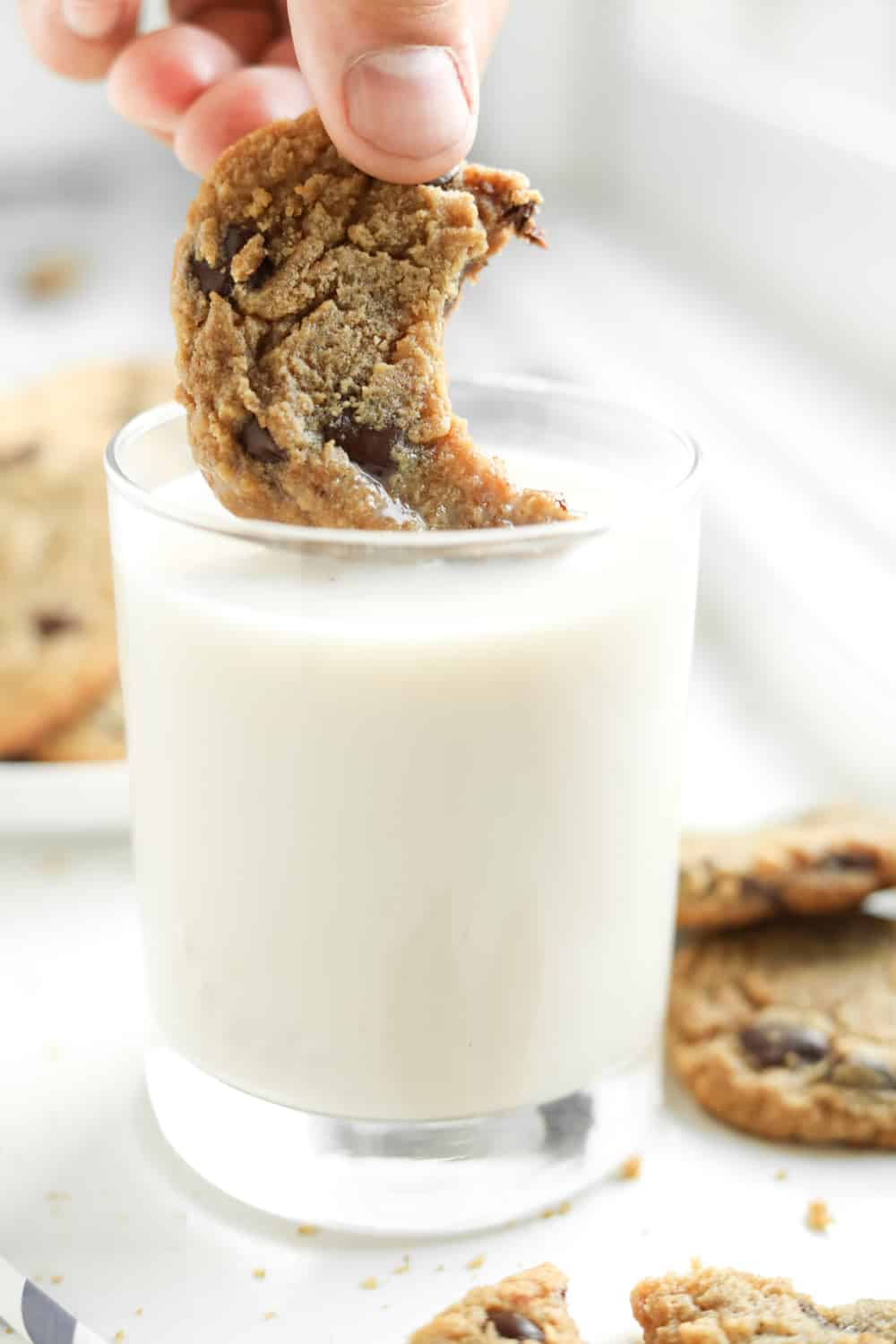 A chocolate chip cookie with a bite taken out of it being dipped into a glass of milk.
