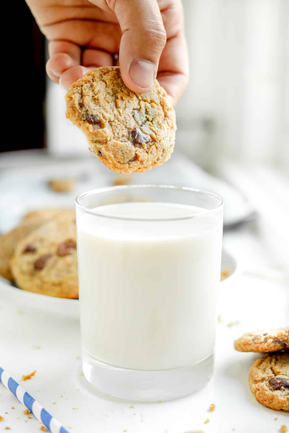 A chocolate chip cookie about to be dipped into a glass of milk.
