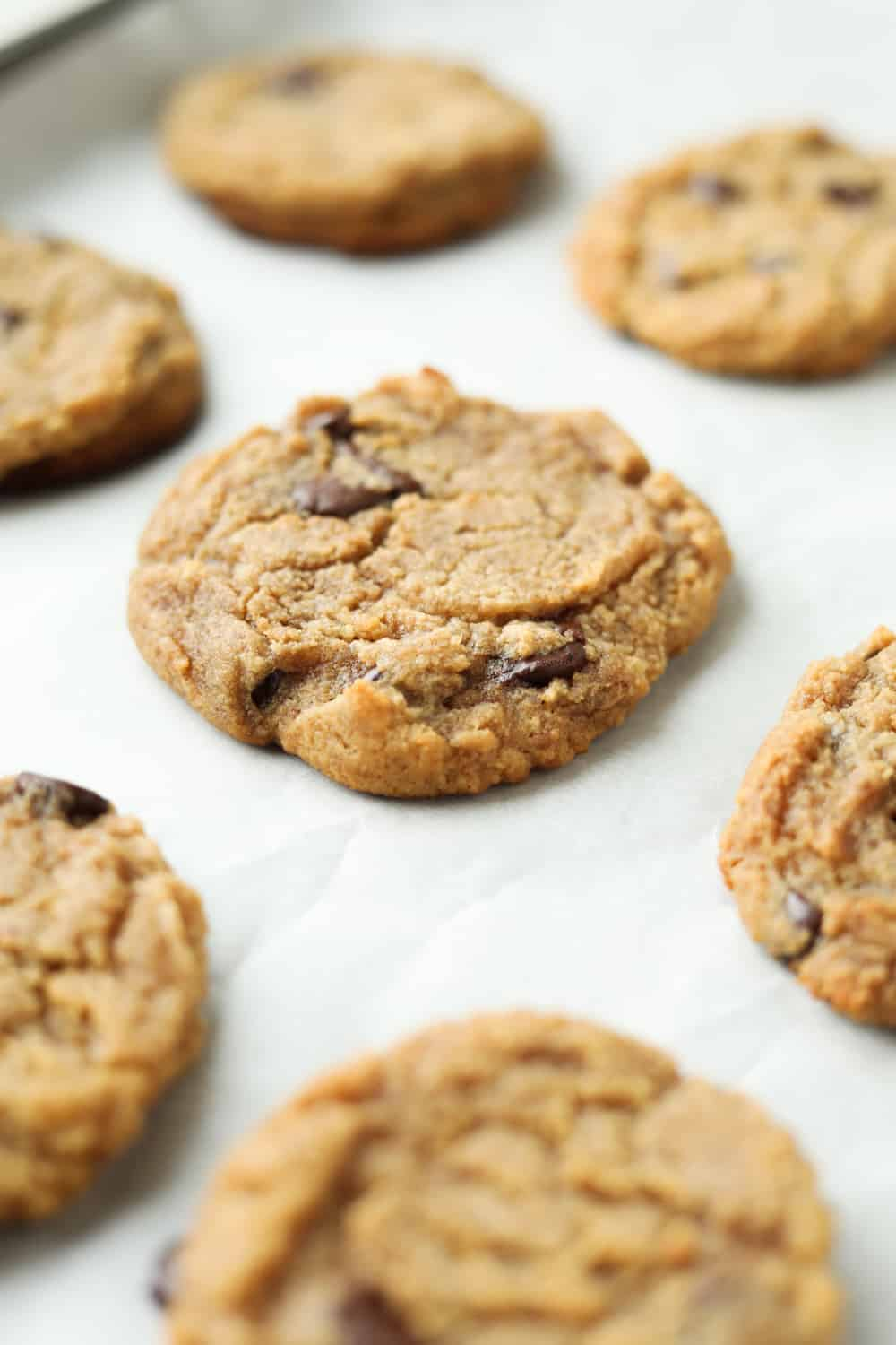 Chocolate chip cookie on a baking sheet lined with parchment paper.