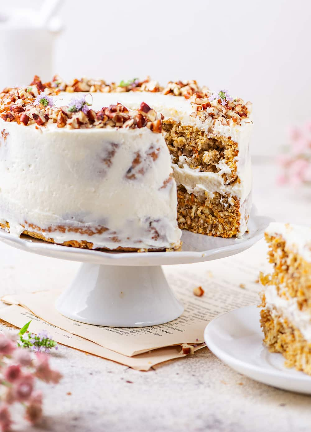 A carrot cake that has had a slice cut from it.