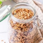 Granola in a glass jar on a white table.