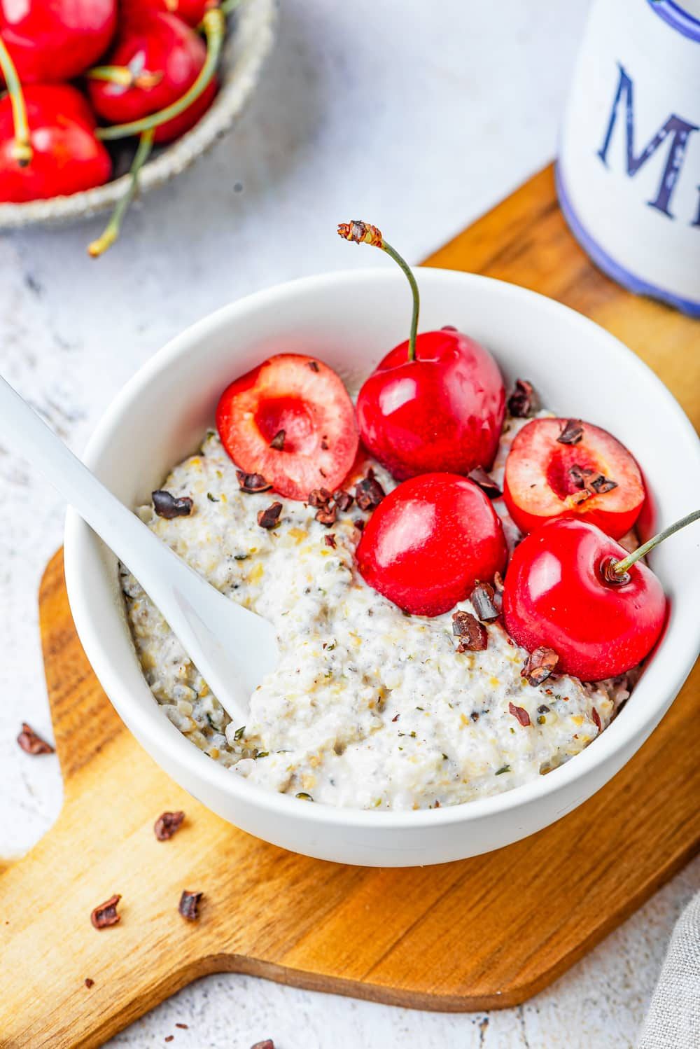 A white bowl filled with oatmeal, low carb chocolate, and a few cherries on a wooden cutting board.