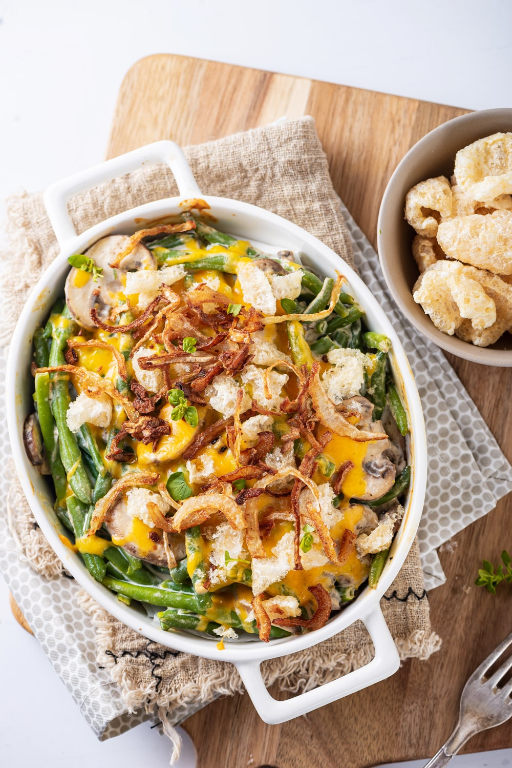 A white casserole dish filled with green beans and mushrooms that have been topped with melted cheese, crispy onions and pork rinds.