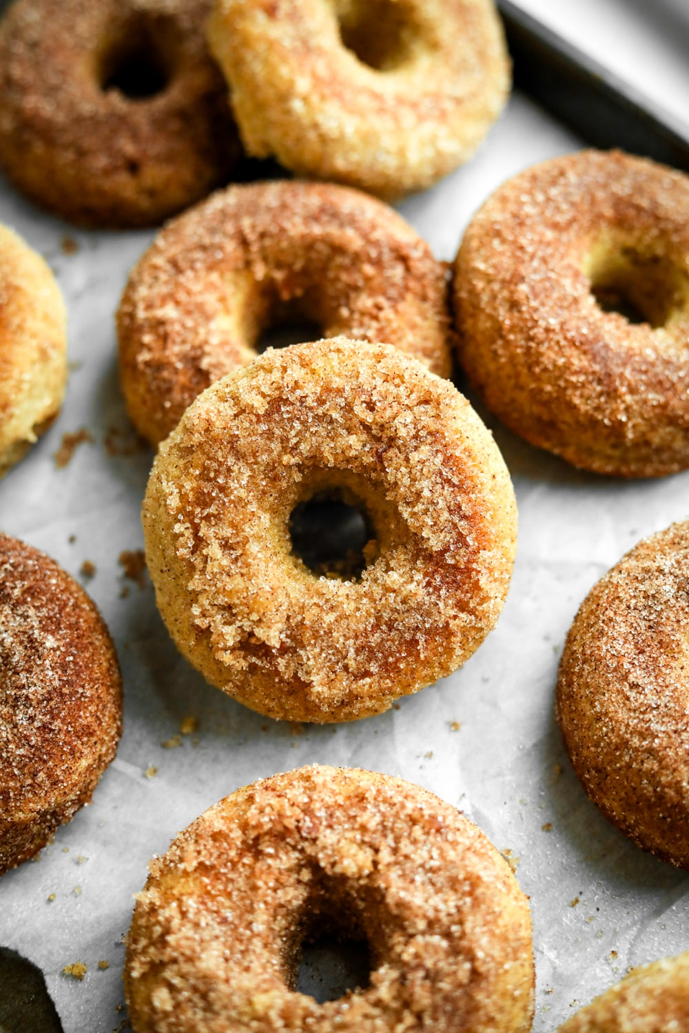 Donuts on a baking sheet lined with parchment paper.