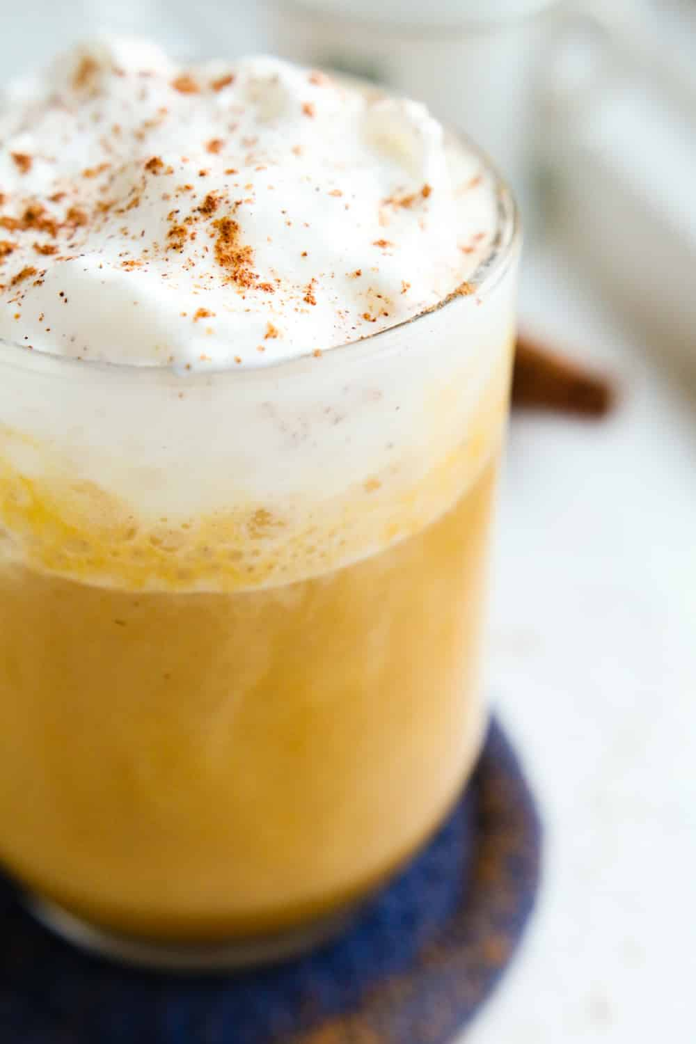 A pumpkin spice latte topped with whipped cream and spices.