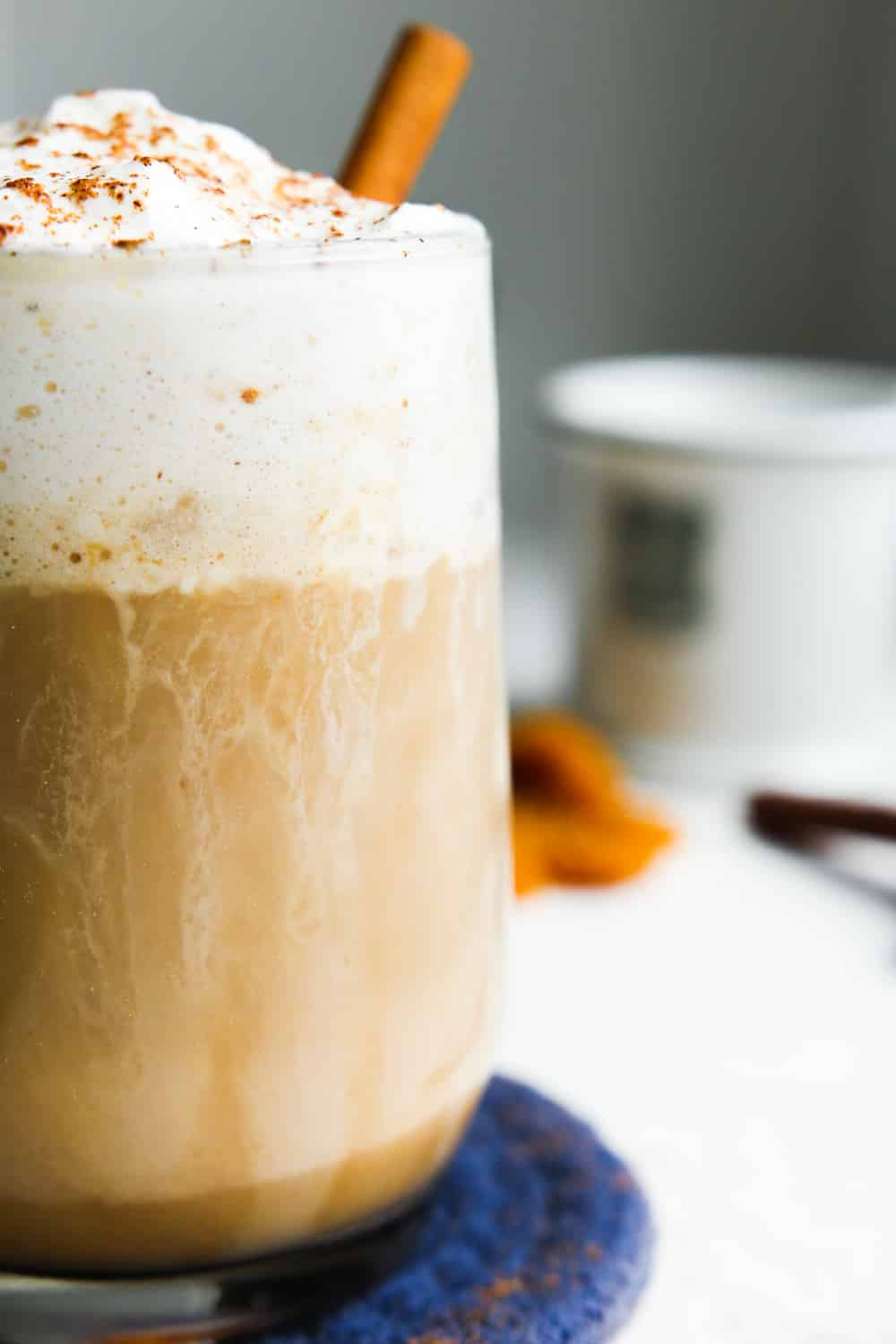 A pumpkin spice latte in a clear glass topped with whipped cream and set on a blue coaster.