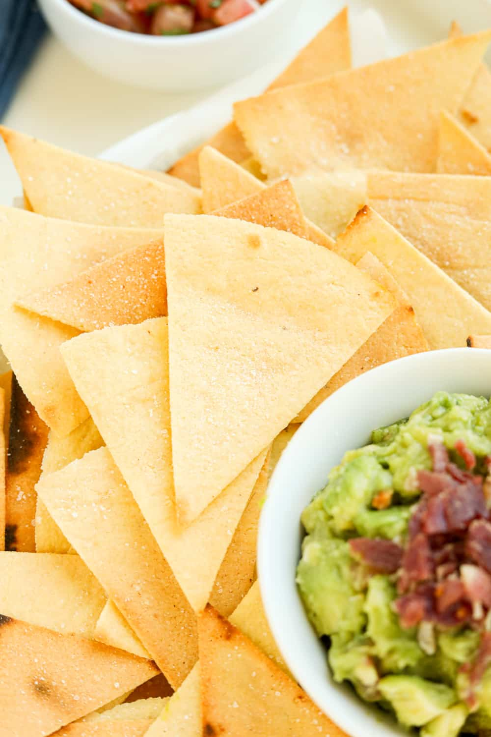 Tortilla chips stacked on top of one another next to guacamole.