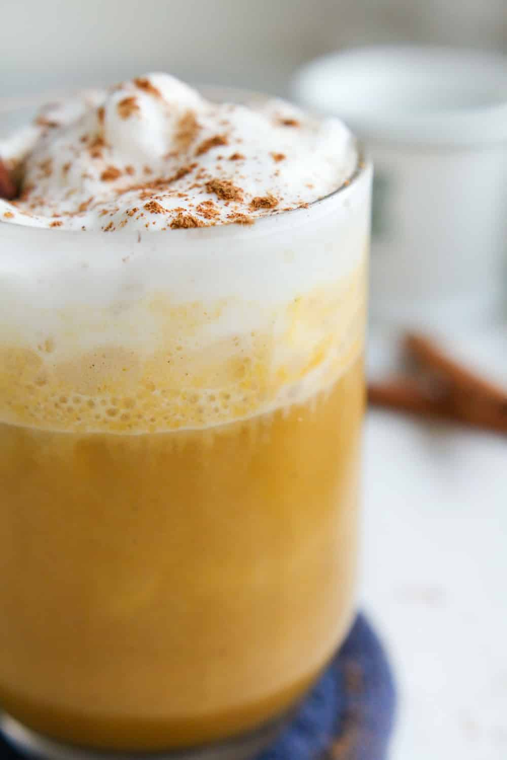 A pumpkin spice latte in a clear cup topped with whipped cream and spices.