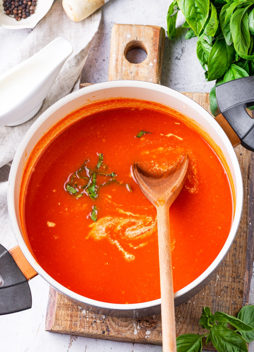 A pot of tomato soup with a spatula inside of it, and it's been set on a cutting board with basil leaves next to it.