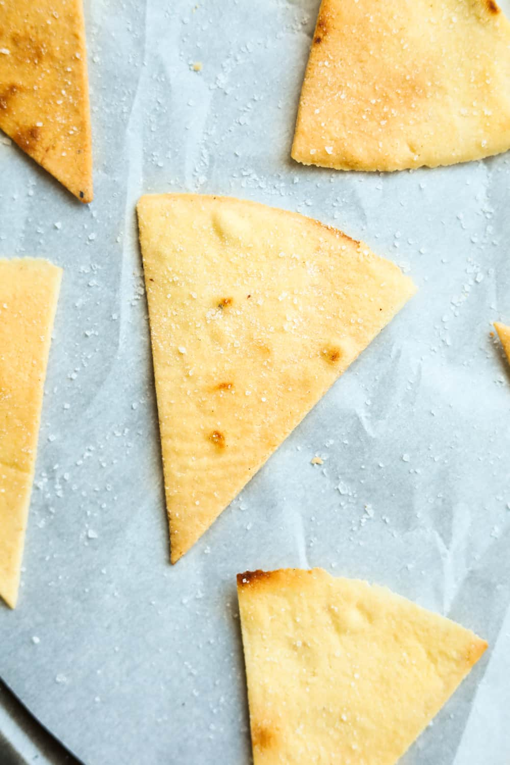 Tortilla chips on a baking sheet lined with parchment paper.