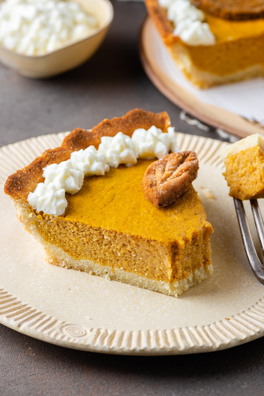 A slice of pumpkin pie with a piece take off of it.