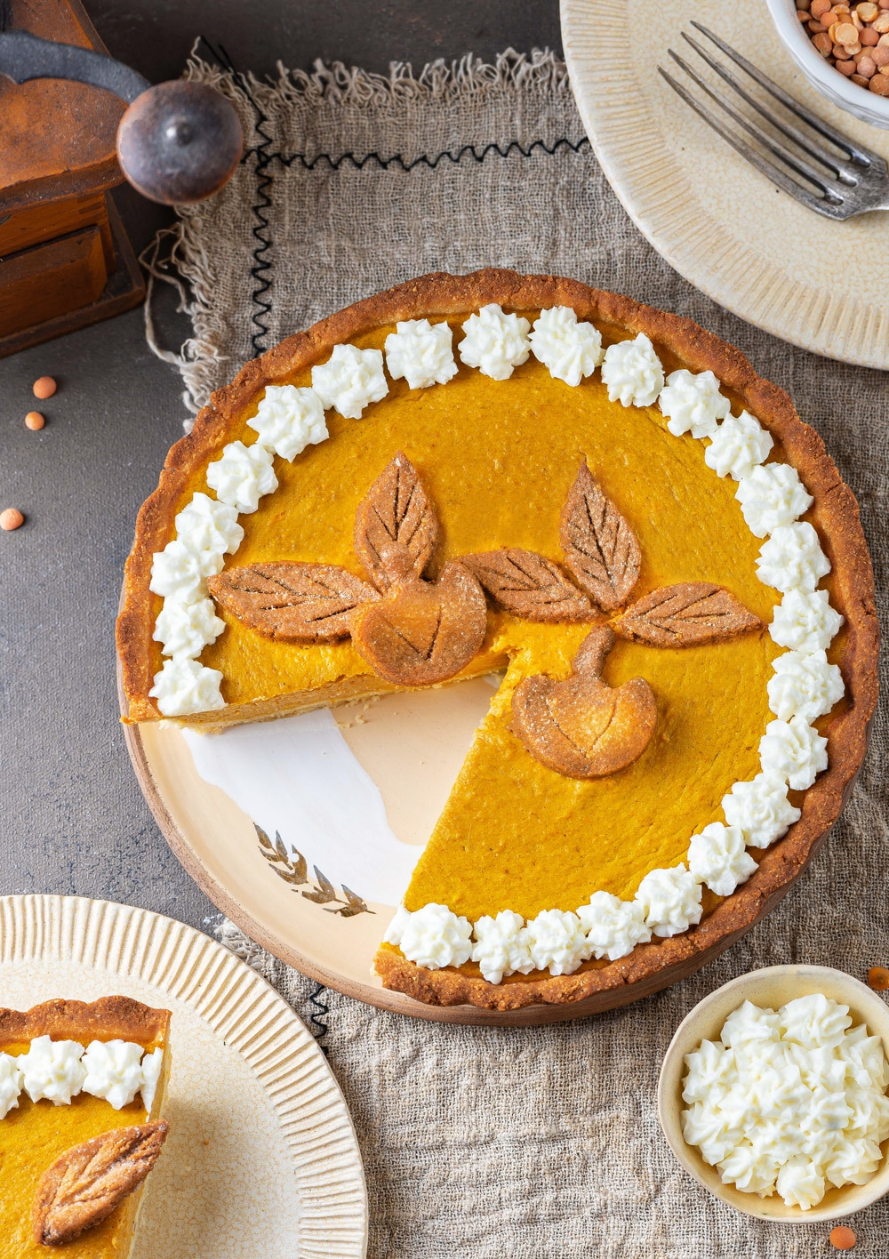A pumpkin pie with a slice missing from it.