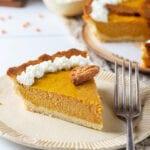 A slice of pumpkin pie on a plate.