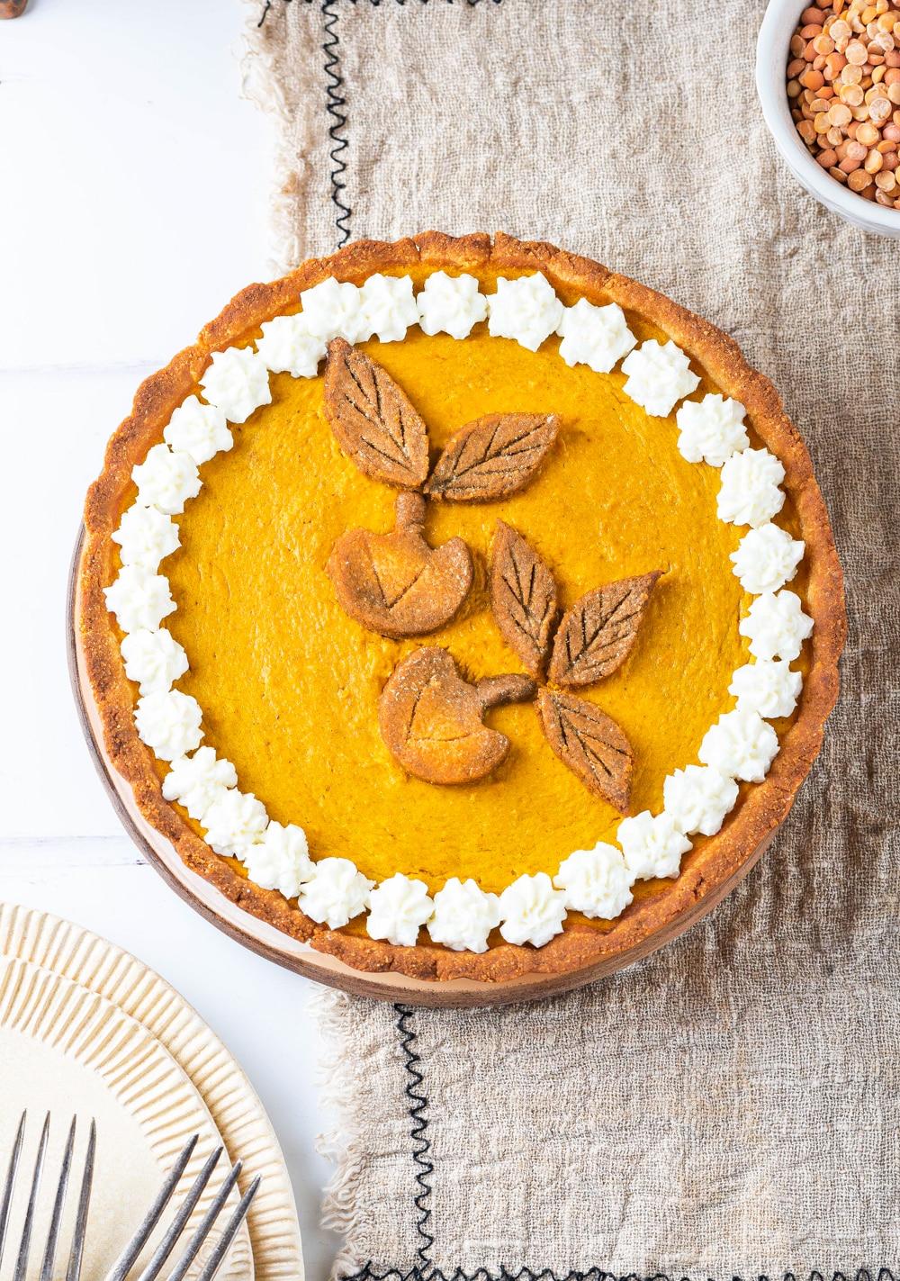 A pumpkin pie set on top of a tan napkin.
