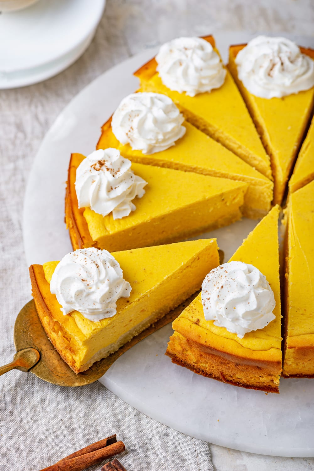 Slices of pumpkin cheesecake topped with whipped cream on a white plate.