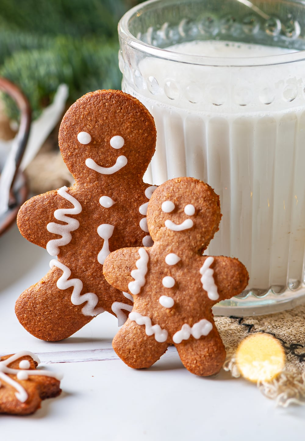 A large gingerbread man cookie and a small one leaning against a glass of milk.