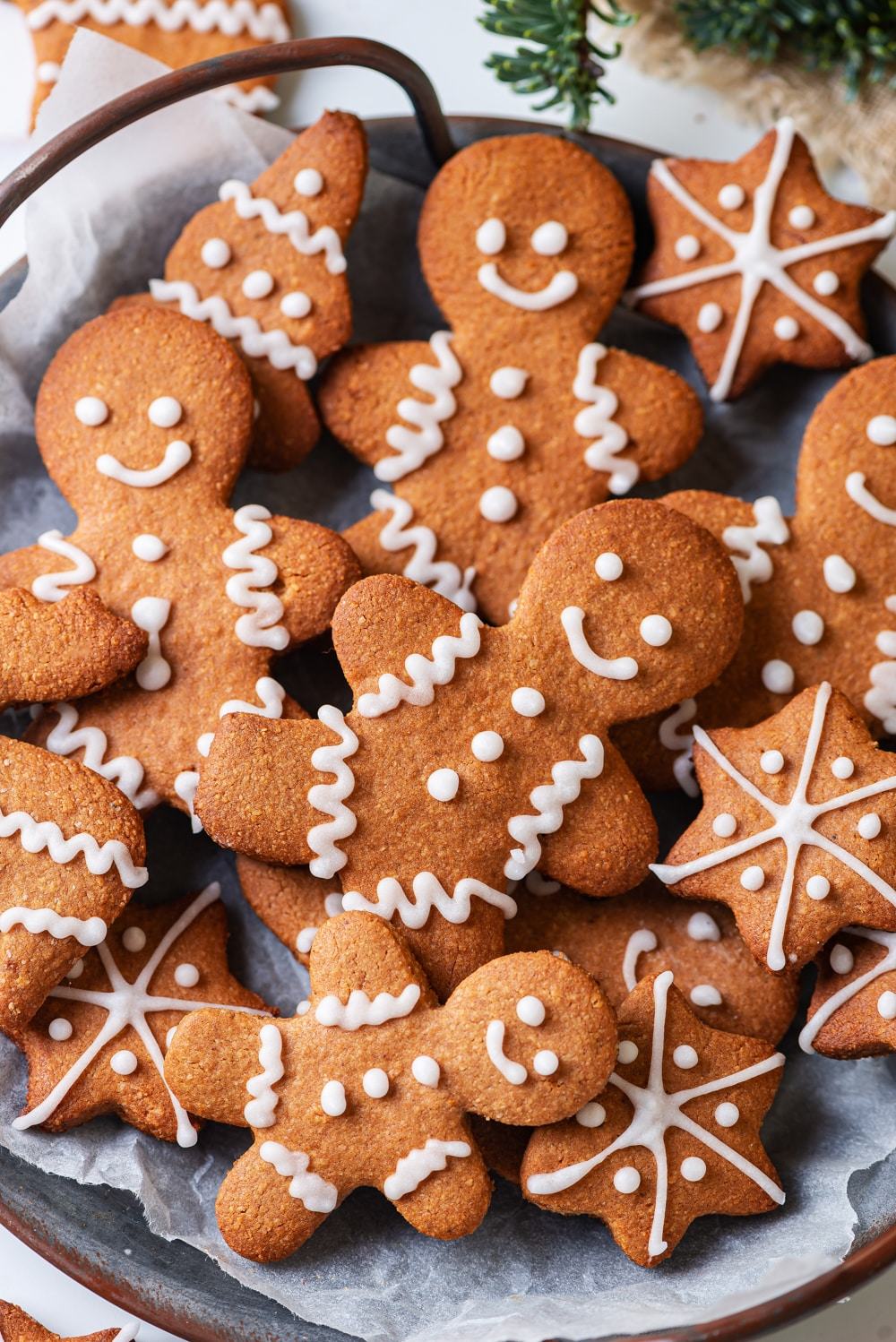 Gingerbread cookies on top of parchment paper on a grey plate.
