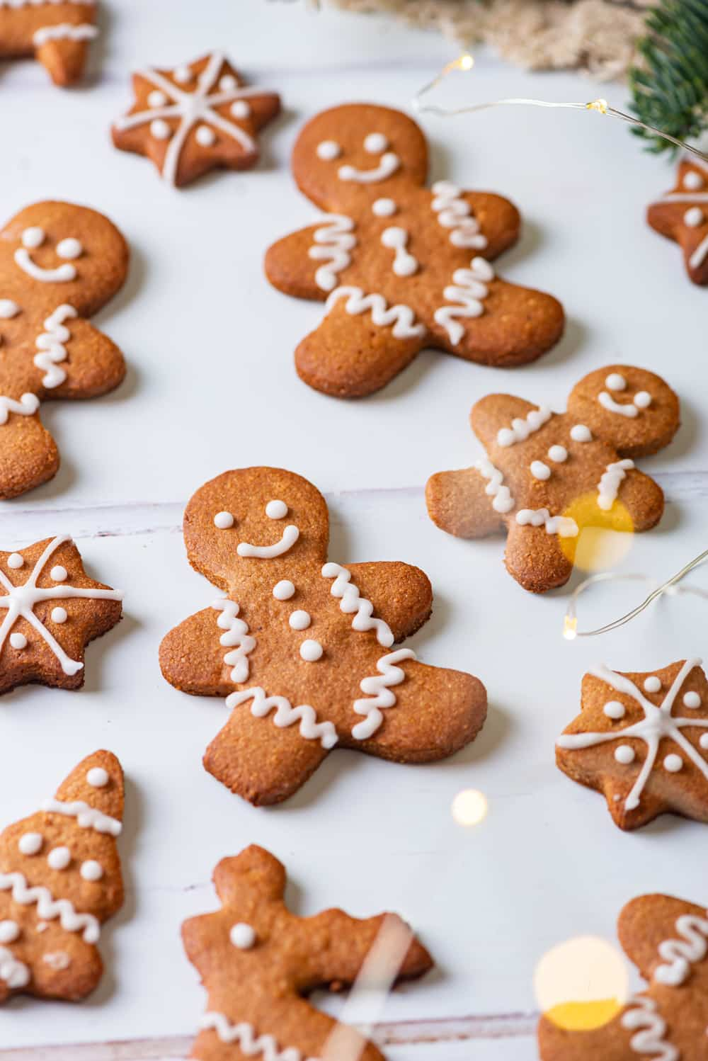 Gingerbread cookies on a white table with gold lights to the right of them.