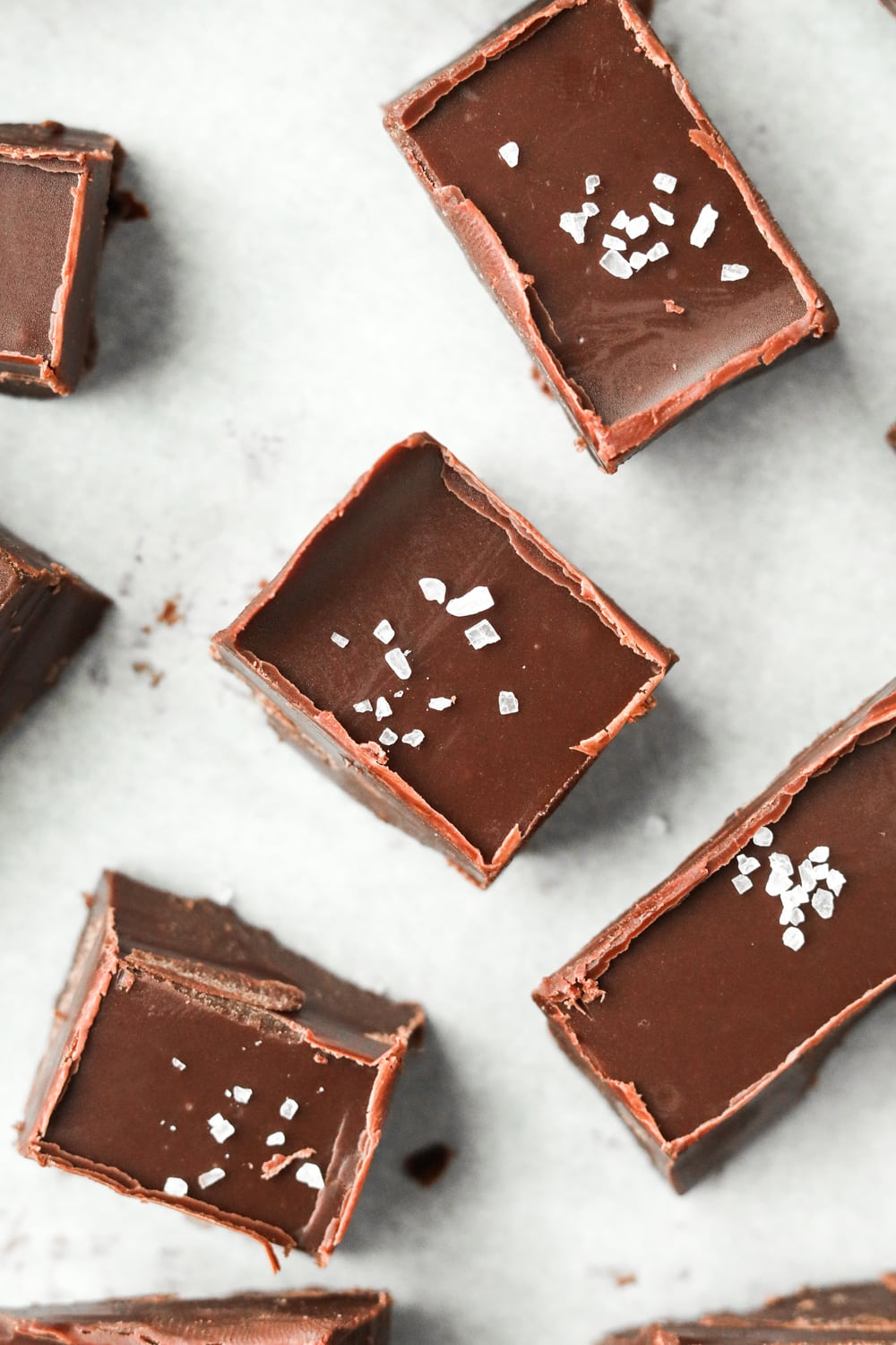 Pieces of chocolate fudge on a sheet of white parchment paper.