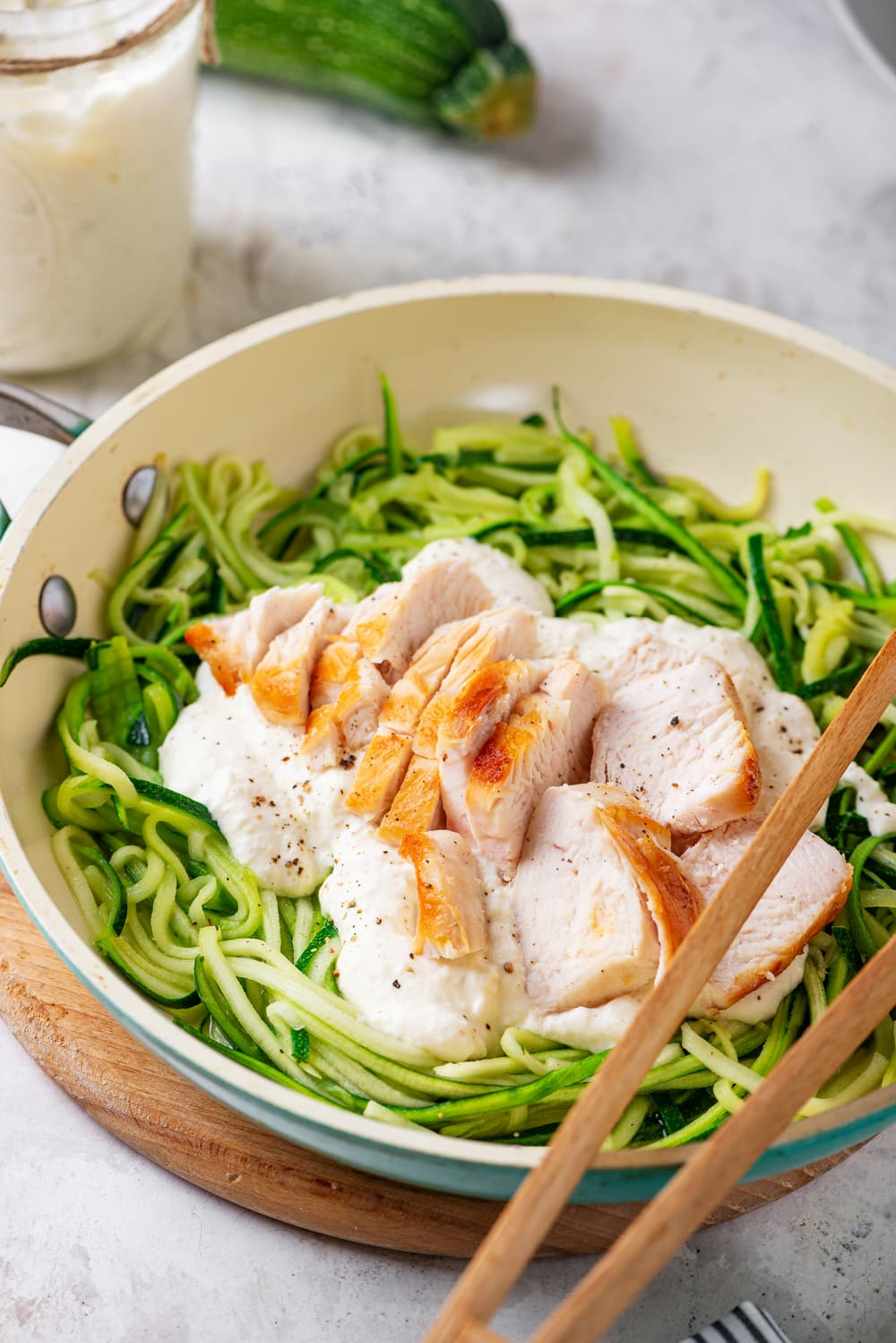 A bowl full of zucchini noodles, alfredo sauce, and cut up chicken.
