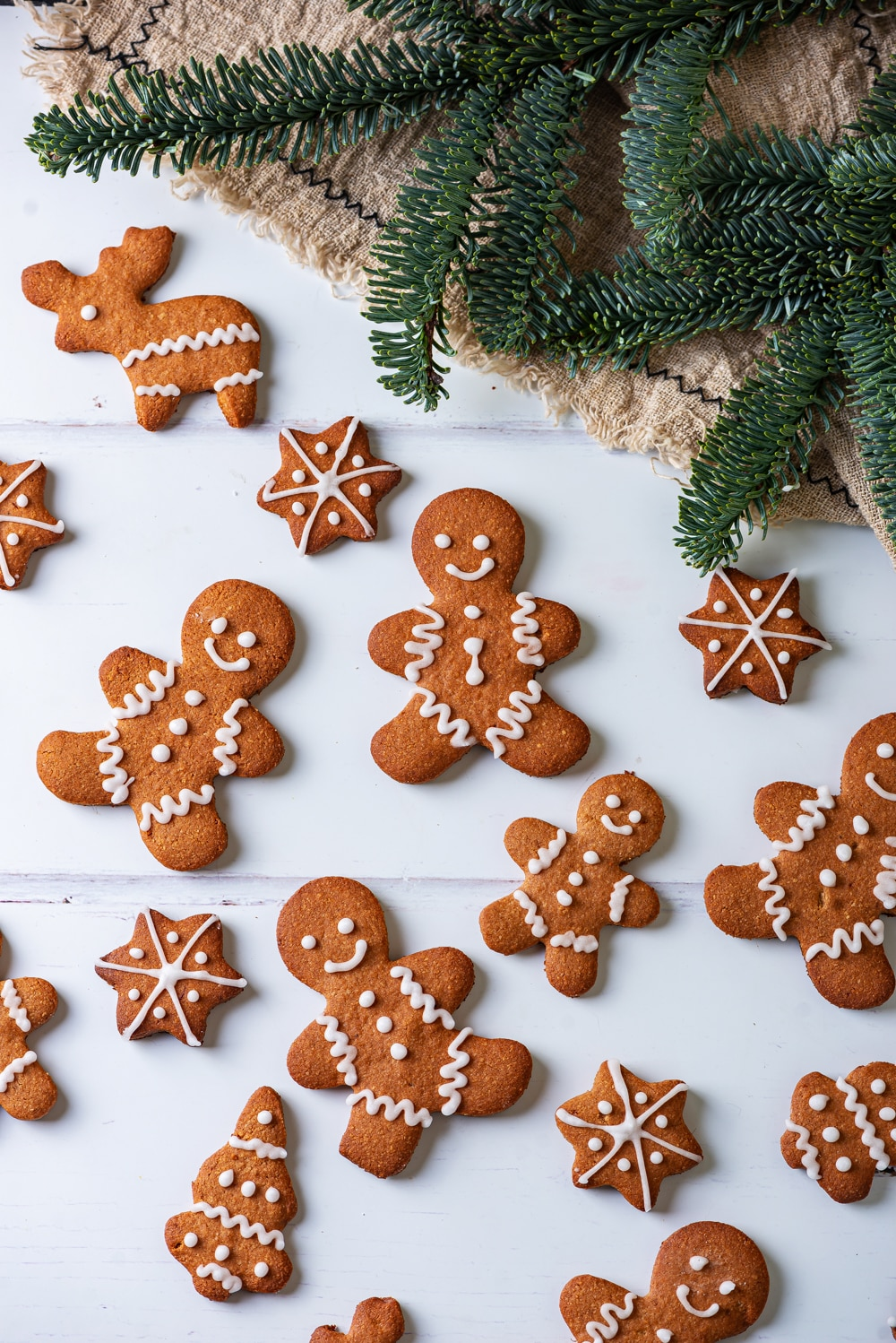 Gingerbread cookies on a white table. Green pine branches are above the cookies.