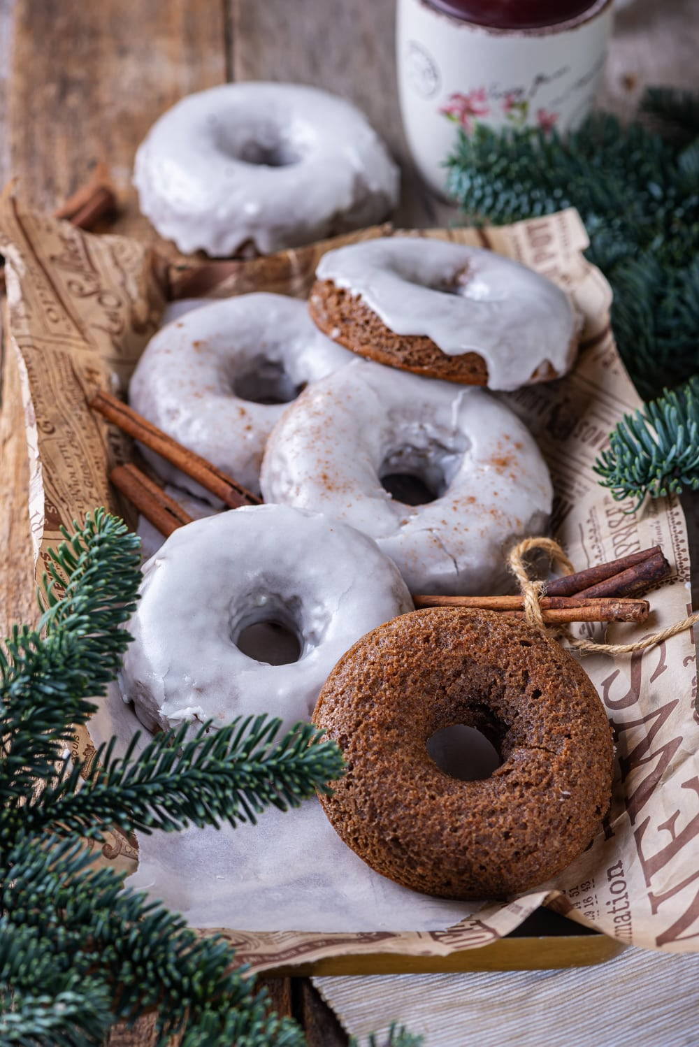 Five glazed gingerbread donuts and one plain gingerbread donut scattered on a piece of paper with cinnamon stick between the donuts. A glazed ginger bread donut is behind the piece of paper.
