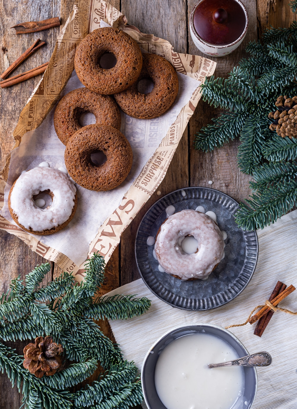 Five gingerbread donuts scattered on paper and a glazed gingerbread donut on a plate next to it. Everything is set on a wooden table with pine branches surrounding the donuts.