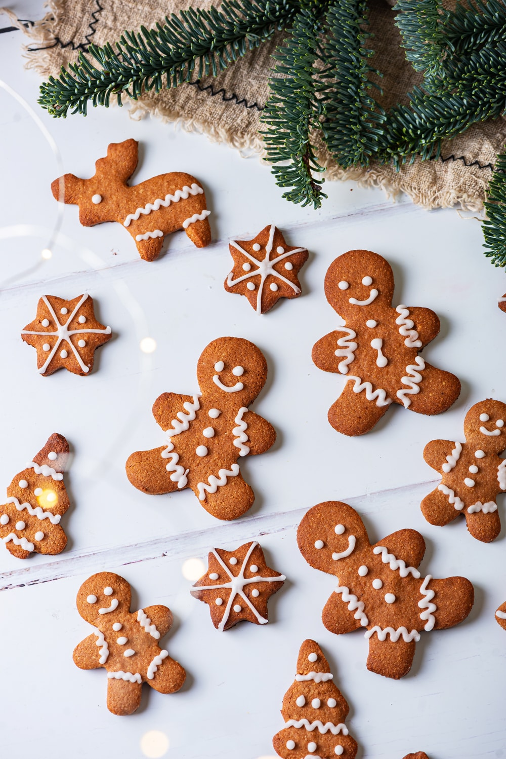 Gingerbread cookies on a white table, with green pine branches above them.
