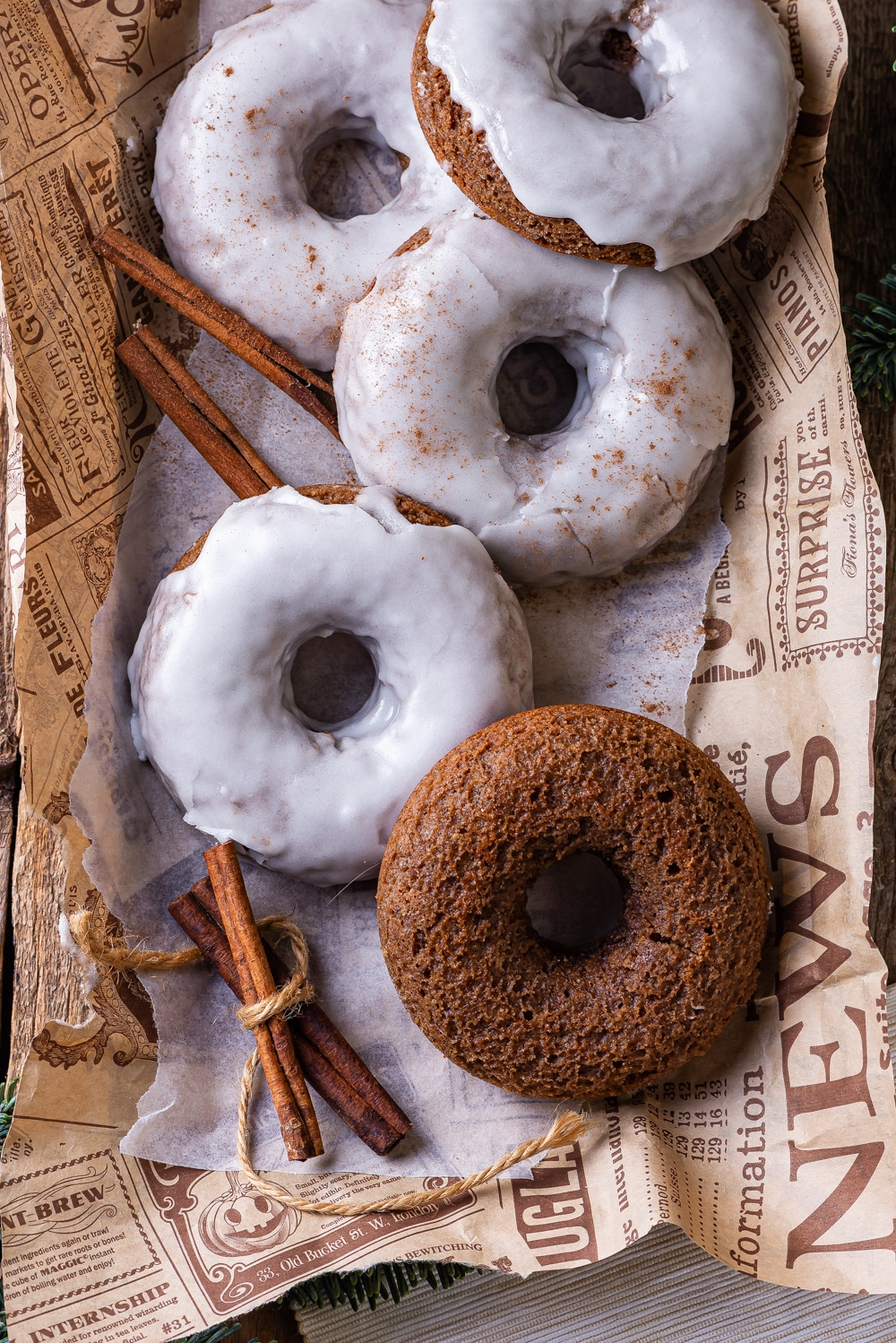 Four glazed gingerbread donuts and one plain gingerbread donut overlapping on a piece of paper. A bundle of cinnamon is next to the plain donut.