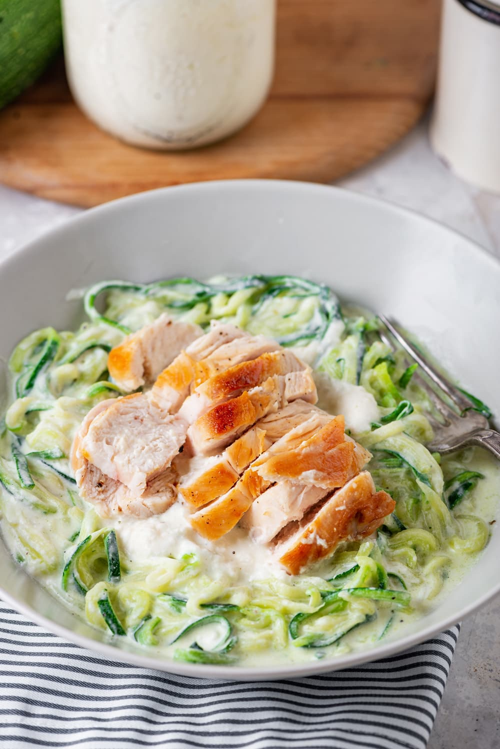 A white bowl filled with chicken on top of zucchini noodles covered in alfredo sauce.