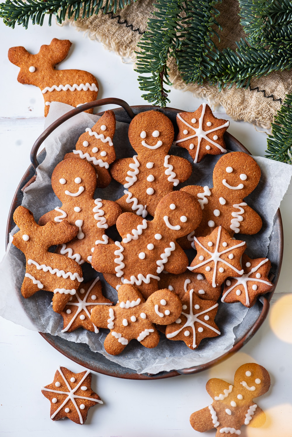 A grey plate with gingerbread cookies on it. Green pine branches are above the plate.
