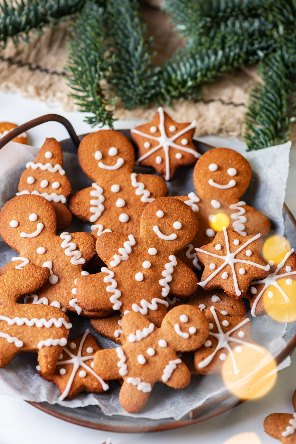 A plate full of gingerbread cookies on white parchment paper.