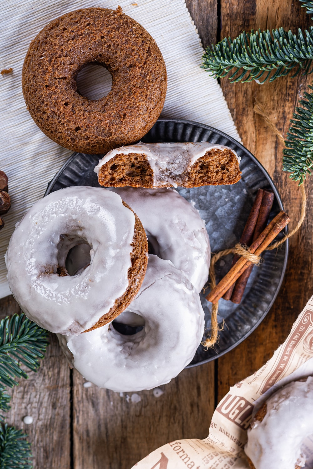 Three glazed gingerbread donuts stacked on top of one another sitting on a plate with half a gingerbread donut facing upwards behind the stack. An unglazed gingerbread donut is sitting on the edge of the plate behind the donuts.