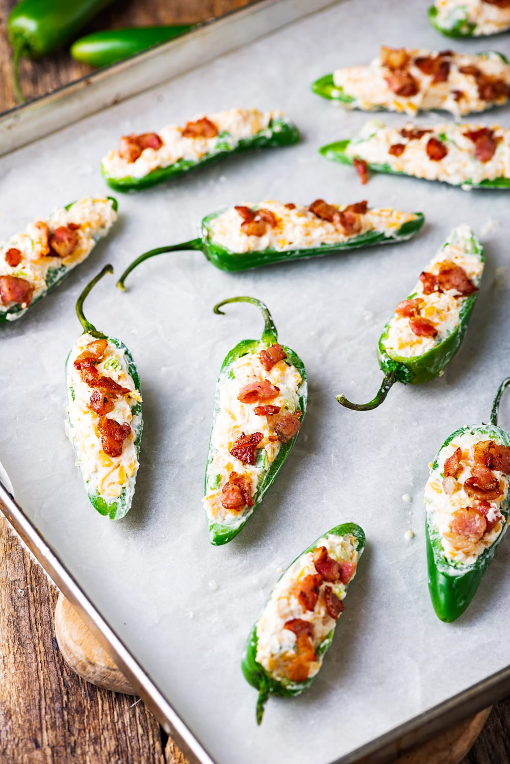 A baking sheet of uncooked jalapenos that have been stuffed with cream cheese and bacon.