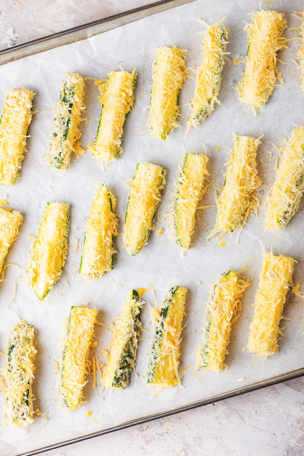 Slices of uncooked zucchini coated in breading laying on a baking sheet.