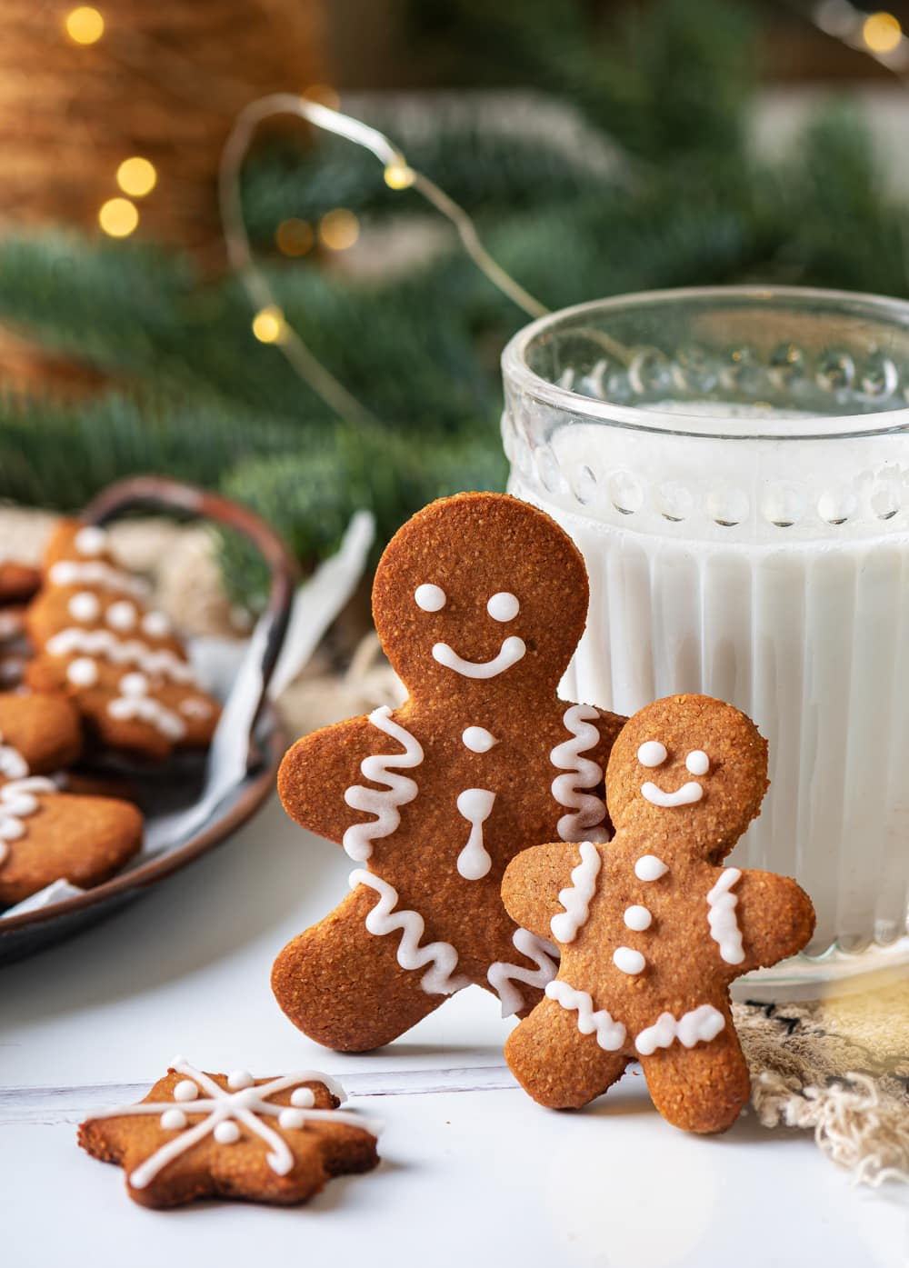 Two gingerbread cookies that are leaned against a glass of milk, with green pine branches and gold lights behind them.