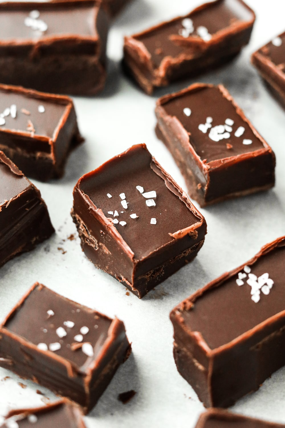 Chocolate fudge topped with coarse salt on a white piece of paper.