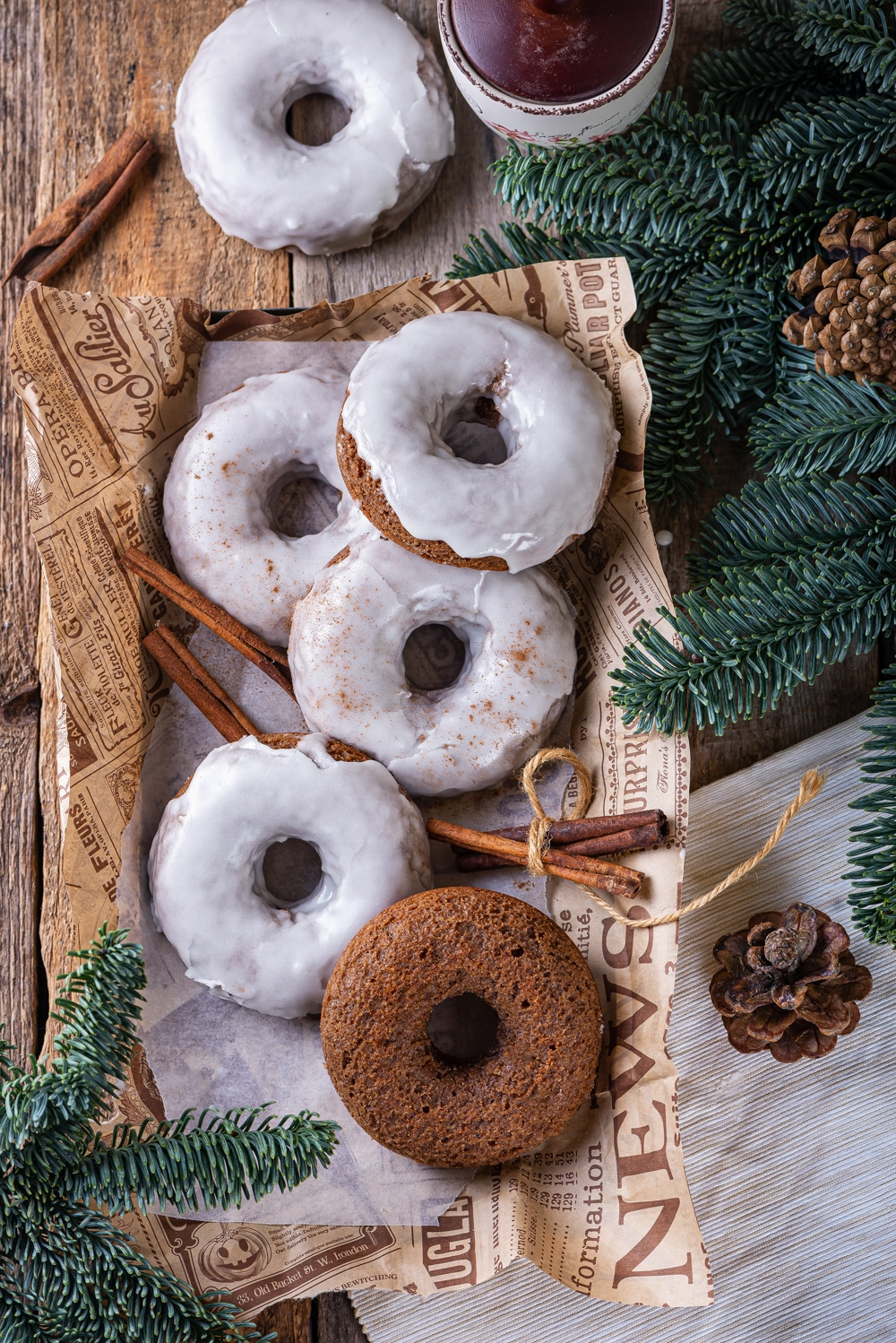 Five glazed gingerbread donuts and one plain gingerbread donut scattered on a piece of paper with two sticks of cinnamon on the sides of the donuts. Pine branches are at the bottom left and top right of the paper. One glazed gingerbread donut is set behind the piece of paper. Everything is on top of a wooden table.